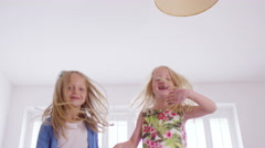 4K 2 Little girls having fun at home, jumping up and down on the bed Stock Footage