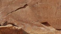 Pan-Red sandstone cliff ancient Indian rock art carved cliff face Utah Desert Stock Footage