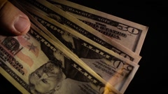 Burning dollars close up over black background Slow motion Stock Footage