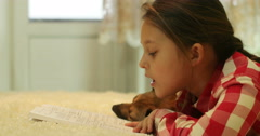 Kid reading a book with a dog Stock Footage