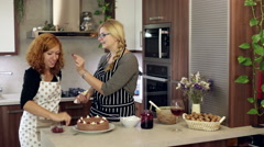 Lovely girlfriends decorating a cake - stock footage