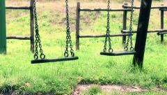 Old vintage empty swings with chains swaying at playground for child Stock Footage