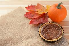 Small pumpkin pie with gourd and autumn leaves - stock photo