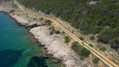 Aerial - Long shot of a man running along the coastal trail, panoramic view - stock footage