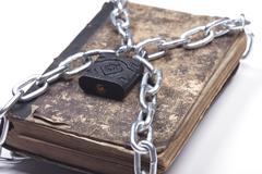 Old vintage tattered book lock with chain white background - stock photo