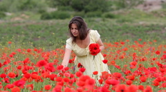 Stock Video Footage of Happy beautiful woman in blossom field arrange a poppy flower in hair, smiling
