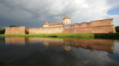 Beautiful fortress reflecting in lake water, dramatic sky, water waving Stock Footage