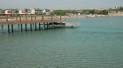 Scene of sunny day with empty wooden pier with resort town on the background. 4k Stock Footage