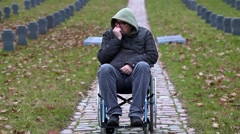 Disabled veteran in wheelchair at cemetery - stock footage