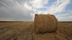 Clouds timelapse on summer field with straw bale Stock Footage