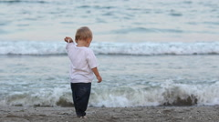 Amusing baby child play and sing on seashore,playfull, beautiful seascape Stock Footage
