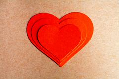 Card for a Valentine's day. Three red paper heart on each other Stock Photos