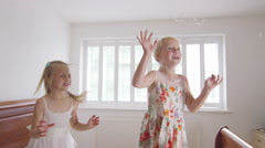 Stock Video Footage of 4K 2 Little girls having fun at home, jumping on the bed with bubbles