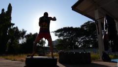 Silhouette Muay Thai Boxer Bouncing On Tire Training Combat Sport Outdoor Gym Stock Footage