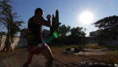 Silhouette Muay Thai Boxer Bouncing On Tire Training Combat Sport Hand Held Stock Footage