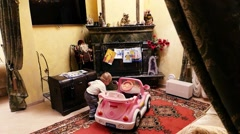 Caucasian Child baby boy toddler kid plays in children's electric vehicle  Stock Footage