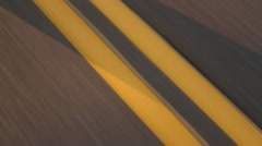 Driving Over Double Yellow Lines on Road at Sunset Stock Footage