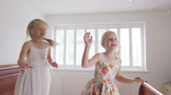 4K 2 Little girls having fun at home, jumping on the bed with bubbles - stock footage