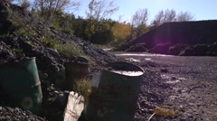Oil drums at abandoned quarry. Dolly Stock Footage