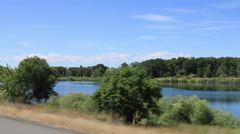 Driving past lake midday Stock Footage