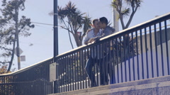 Gay Couple Lean Against Railing And Kiss, Then Smile Stock Footage