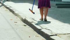 Cleaning the streets. Woman sweeping the sidewalk and flying dust in air  Stock Footage
