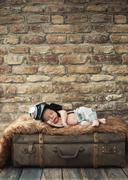 Little pilot baby sleeping on the luggage - stock photo