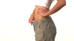 Slim girl in big trousers, showing her lose weight, on white Stock Footage