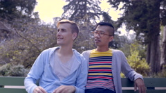 Cute Gay Couple Take Fun Selfies Together On Park Bench Stock Footage