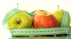 Green, fresh apple with measuring tape on white, rotation - stock footage