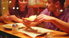 A young couple eating at a downtown pizzeria Stock Footage