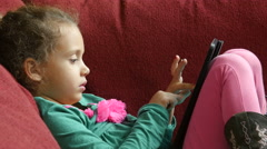 5 year old girl on a couch using an ipad/tablet Stock Footage