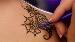 Art of mehendi. Master works on models back, close up Stock Footage