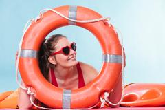 Stock Photo of Happy woman in sunglasses with ring buoy lifebuoy.