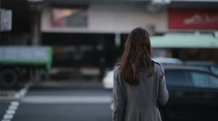 Beautiful young girl waiting at a crosswalk Stock Footage