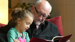 Grandfather reading to his granddaughter Stock Footage