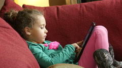 Little girl using an ipad/tablet on a couch Stock Footage