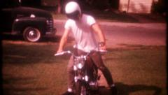 2711 - teenage boy puts on a helmet & rides motorcycle - vintage film home movie Stock Footage