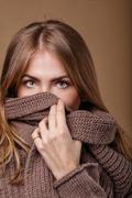 Girl hides her face in a warm sweater. We see only the eyes. Stock Photos