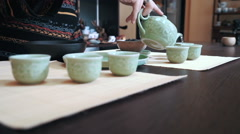 Master of tea pouring water in pialas at tea ceremony - stock footage