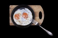 Scrambled eggs in iron skillet, top view isolated black - stock photo