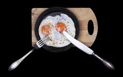 Scrambled eggs in iron skillet, top view isolated black Stock Photos
