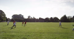 Caucasian boys playing football together at a soccer ground. Shot on RED Epic. Stock Footage
