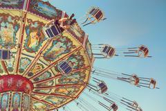 Wave Swinger ride against blue sky - stock photo