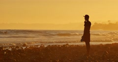 Cinemagraph - Silhouette man standing ocean beach waves sunset 4K Motion Photo Stock Footage