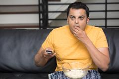 Closeup portrait, young man in yellow t-shirt, sitting on black leather couch - stock photo