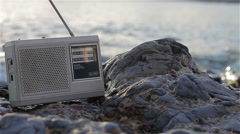 Listening a vintage FM/AM radio on the beach Stock Footage