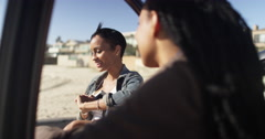 Handheld over the shoulder shot of two women friends talking and leaning against - stock footage