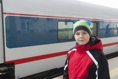 Stock Photo of sad teenager boy standing near train