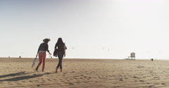 Two best friends walking out towards the ocean across a large sandy beach with Stock Footage